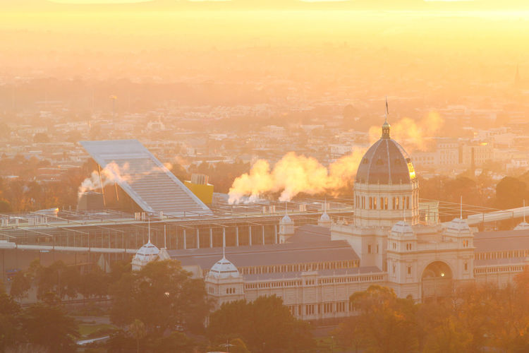 A foggy morning of the Royal Exhibition Hall Royal Exhibition Building Architecture Building Building Exterior Built Structure City Cityscape Fog Foggy Morning Government High Angle View History Nature No People Orange Color Outdoors Sky Sunlight Sunset Tourism Travel Travel Destinations Tree
