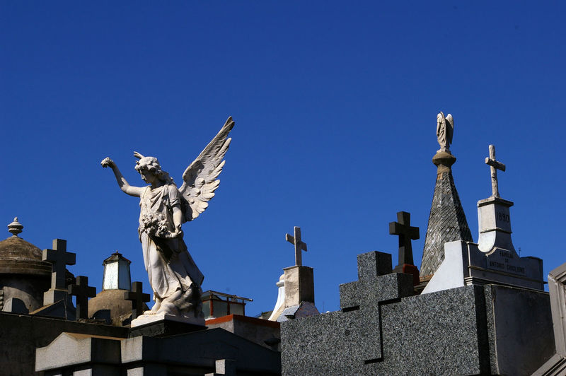 Low Angle View Of Statue And Cross In Cemetery Against Clear Blue Sky