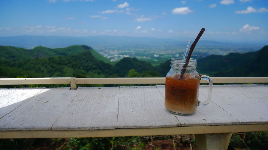 Close-up of drink on table against mountain