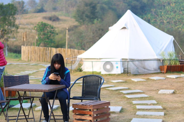 Young woman using smart phone while sitting on chair at campsite