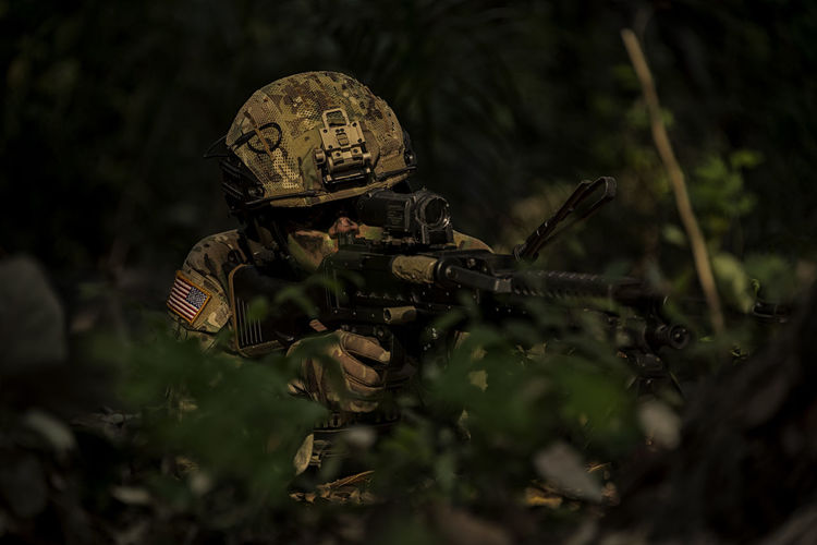 Soldier holding rife by plants in forest
