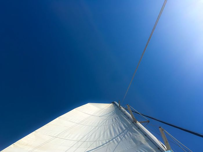 Mast and canvas of sailboat against sky