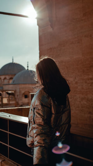 Rear view of woman in jacket looking at city buildings