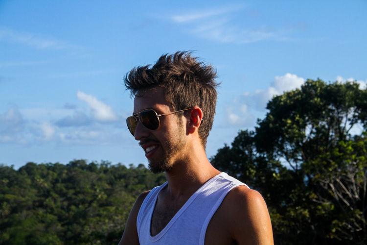 Smiling man wearing sunglasses against sky