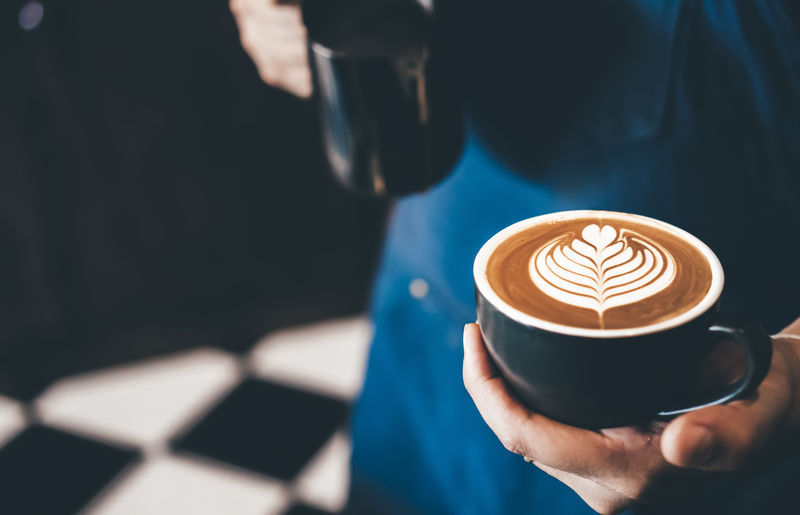 Midsection of barista holding cappuccino