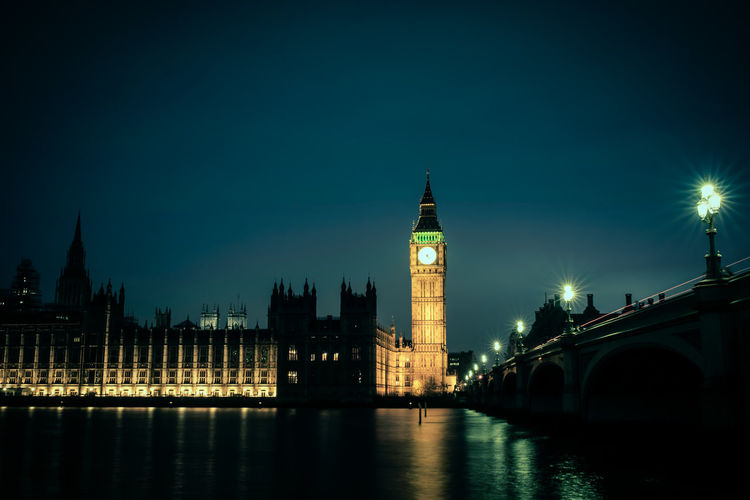 Illuminated big ben with thames river against sky