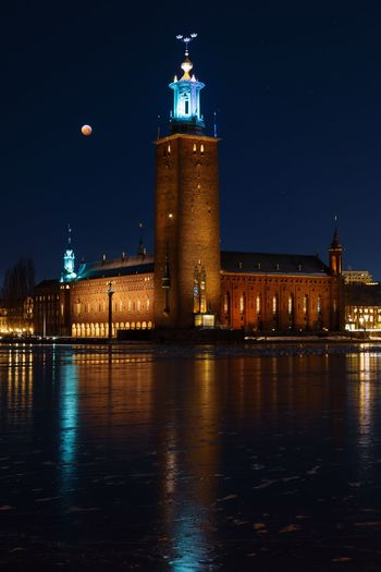 Blood moon over illuminated buildings stockholm city hall at night