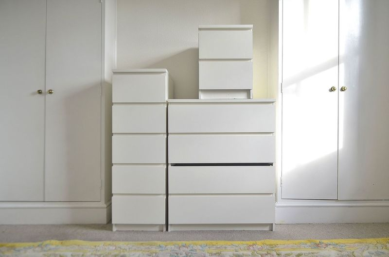 Stack of white boxes amidst closets against wall at home