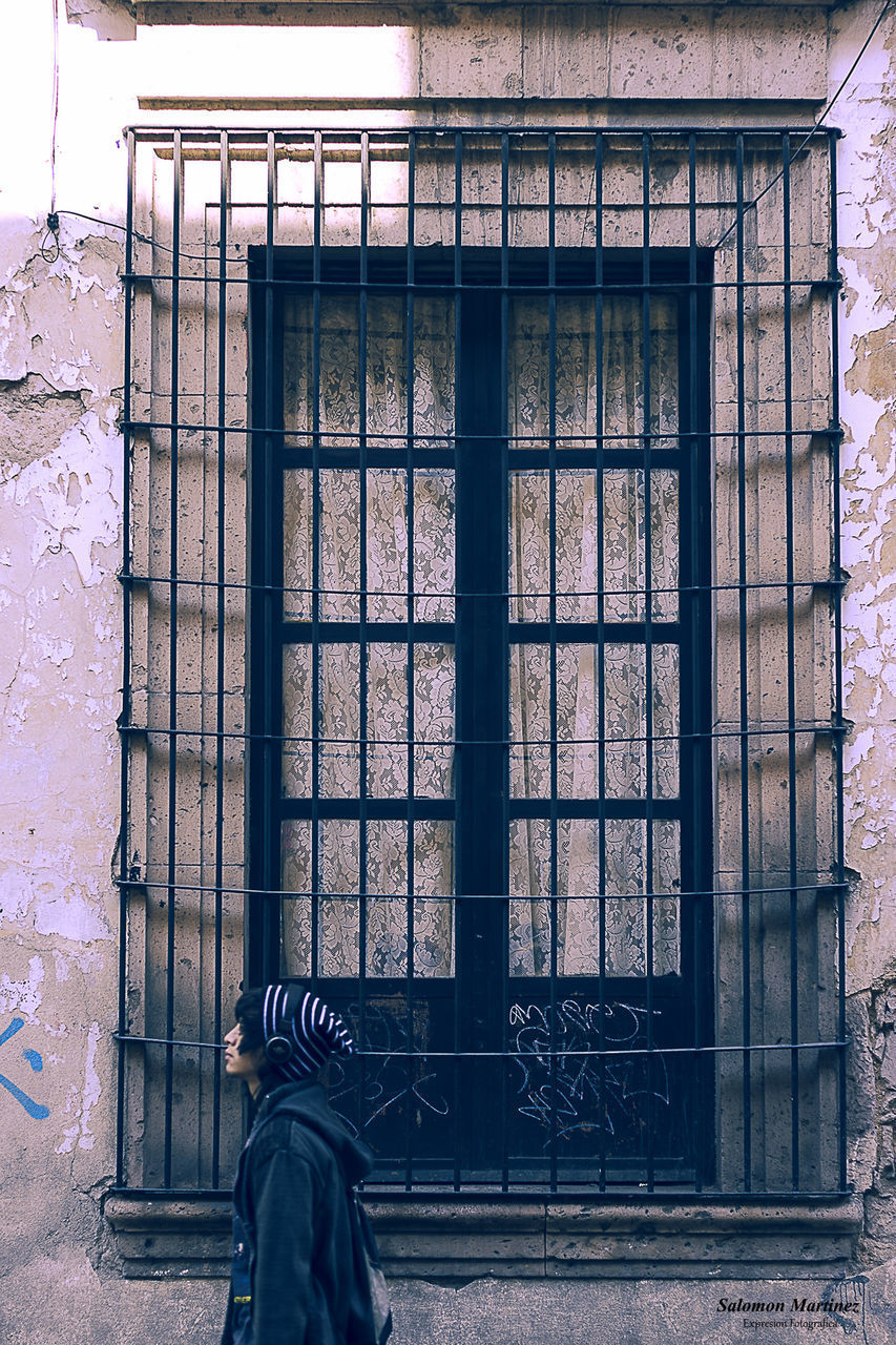 built structure, architecture, real people, window, building exterior, one person, building, day, glass - material, rear view, lifestyles, men, transparent, outdoors, clothing, wall - building feature, closed, leisure activity, standing