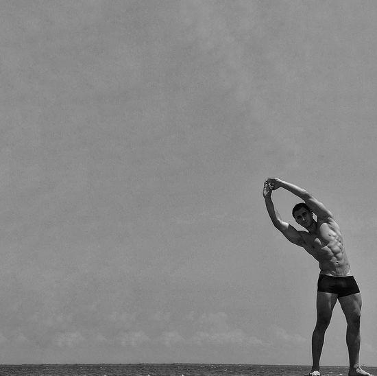 Full length of shirtless man exercising against sky