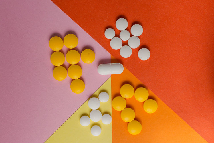 Indoors  Pill Medicine Dose Healthcare And Medicine Studio Shot No People Large Group Of Objects Still Life Colored Background Multi Colored Close-up High Angle View Orange Color Directly Above Nutritional Supplement Choice Yellow Capsule Geometric Shape Pill Container