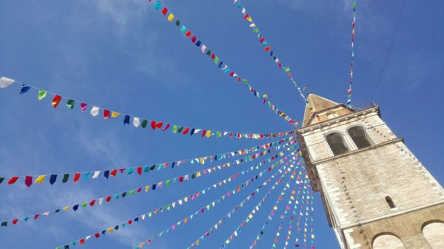 Low angle view of buntings decorated at church in fossalta di portogruaro