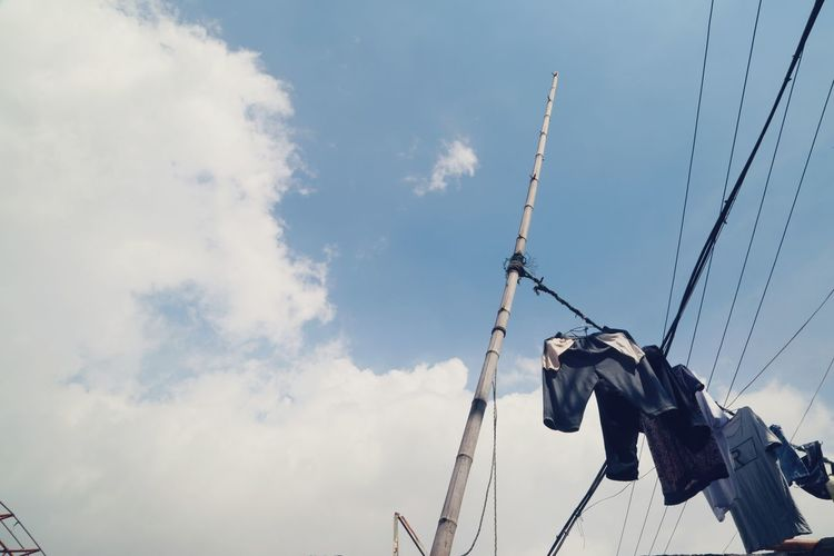Low angle view of clothesline against cloudy sky during sunny day