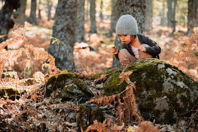 Girl crouching on rock in forest during autumn