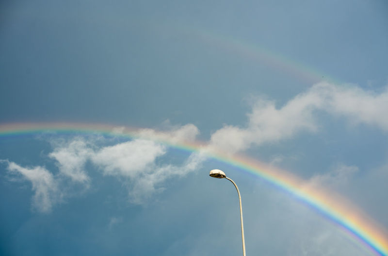 Low angle view of rainbow over street light