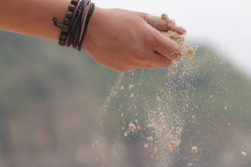 Cropped image of person hand sprinkling sand