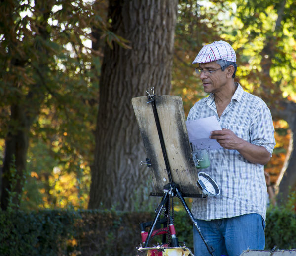 Painter Standing By Tree
