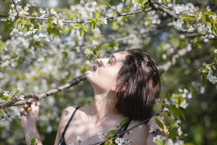 Close-up of young woman by flowering tree