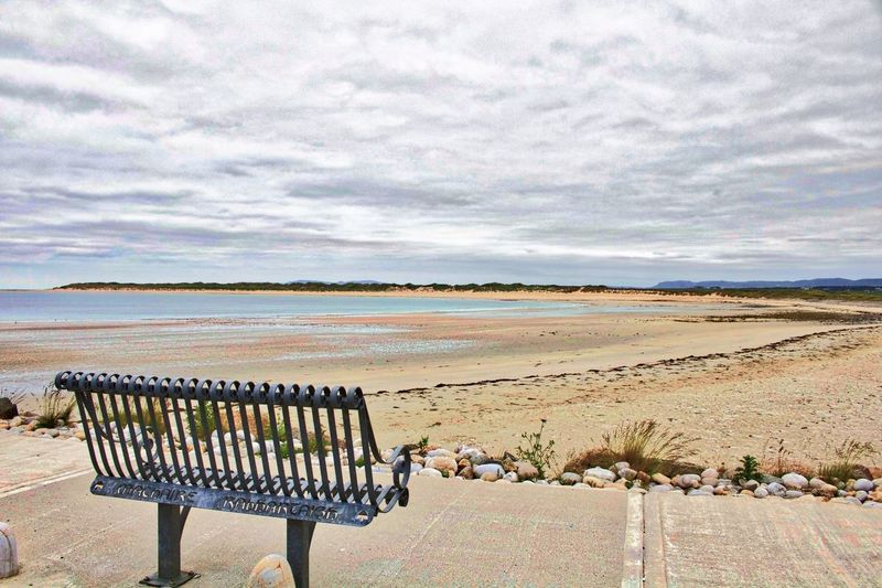 Empty park bench at beach against cloudy sky on sunny day
