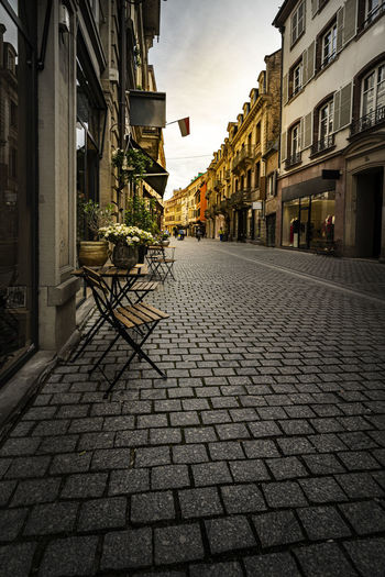 Cobblestone street amidst buildings in city