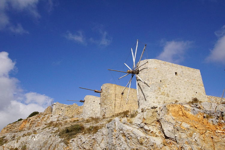 Low angle view of windmill on mountain against sky