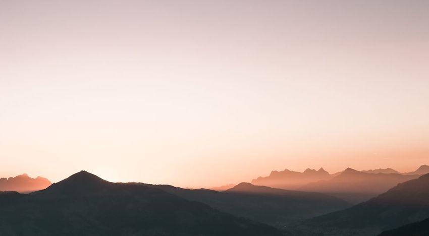 Rising sun behind Mountains Romantic Romantic Sky Sunset Beauty In Nature Mountain Sky Scenics - Nature Mountain Range Tranquility Tranquil Scene Landscape Nature Silhouette Environment Non-urban Scene Idyllic Clear Sky No People Orange Color Sun Majestic
