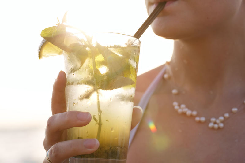 Midsection Of Woman Drinking Mojito