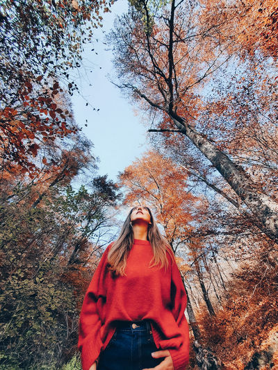 Low section of woman standing by plants during autumn
