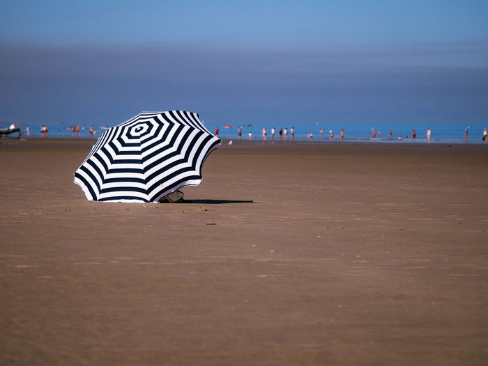 Summer day at the beach with an umbrella in the foreground Bathing Summer Views Beach Beachlife Beauty In Nature Cloud - Sky Day Horizon Incidental People Low Tide Nature Outdoors Sand Scenics - Nature Sea Sky Striped Sun Protection Sunbathing Tranquil Scene Tranquility Travel Destinations Umbrella Water Waterline