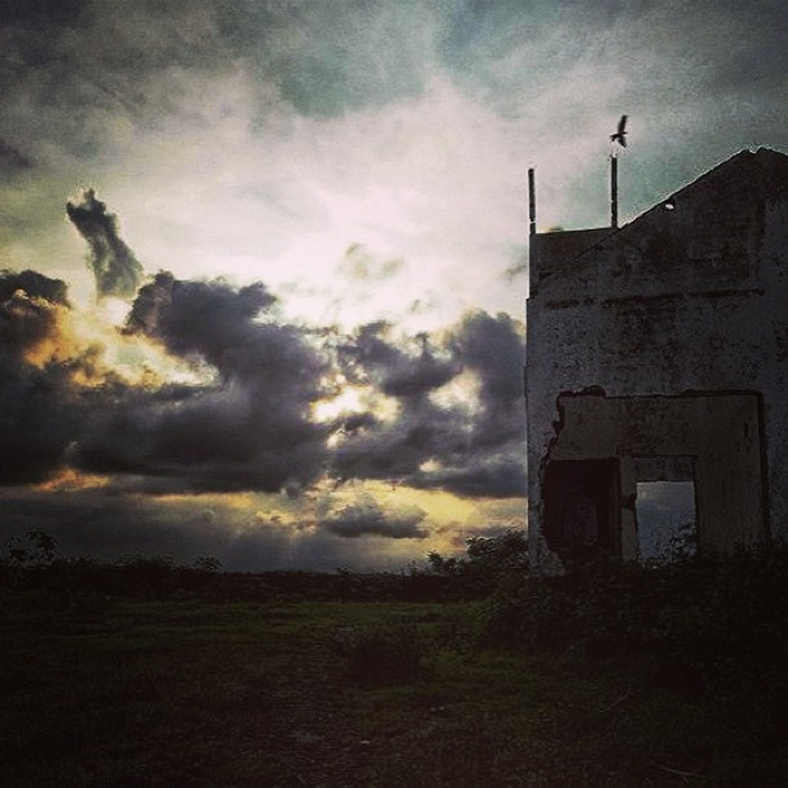 sky, cloud - sky, architecture, building exterior, built structure, cloudy, sunset, cloud, field, low angle view, silhouette, weather, house, nature, outdoors, landscape, no people, overcast, dusk, building