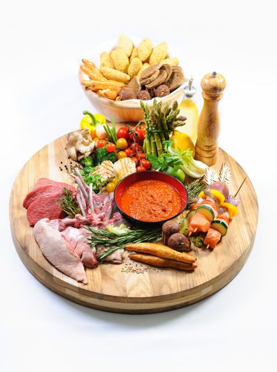 Abundance of raw food on a wooden board and basket of bread over white background Beef Canapé Ingredients Pork Raw Meat   Beef Bread Canapes Chicken Fillet Close-up Fillet Food Food And Drink Fresh Healthy Eating Indoors  Meat No People Raw Chicken Raw Food Steak Studio Shot Vegetable White Background Wooden Board