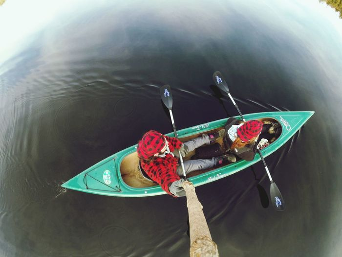 Overhead view of two people canoeing in water