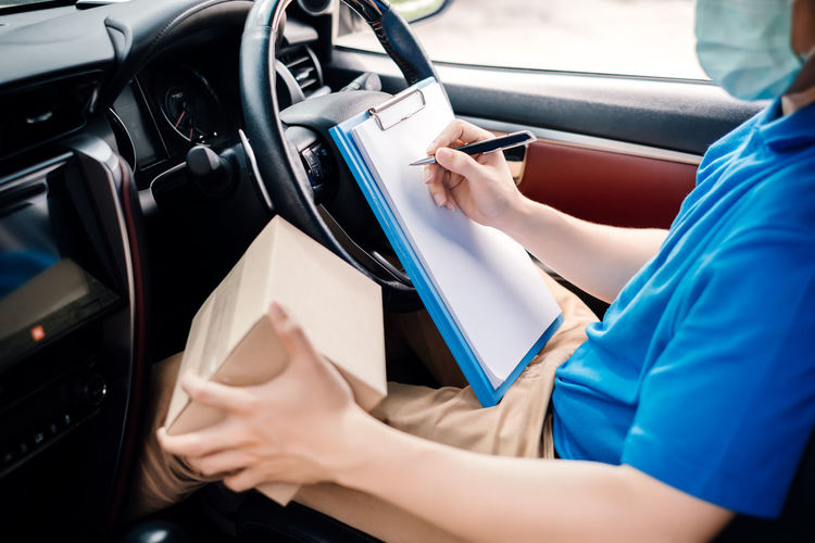 Midsection of woman holding smart phone in car