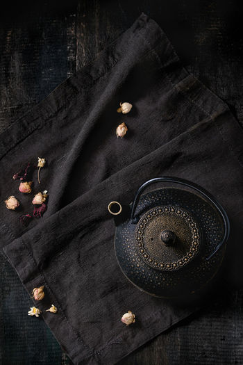 Black iron asian style teapot with dry tea roses on black textile napkin over old wooden table. Flat lay. Black Background Copy Space Dark Kettle Asian Style Black Cloth Dark Food Photography Directly Above Drink Dry Roses Flat Lay Metal Minimalism Object Rose Buds Still Life Tea Kettle Tea Roses Tea Time Teapot Textile Top View Utensil