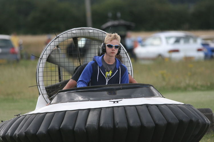 Teenager driving hovercraft on grass