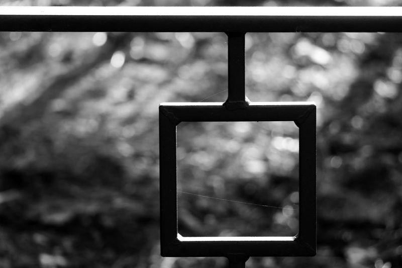 Close-up of metal railing against window