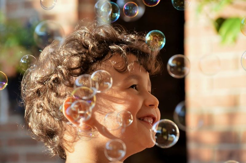 Cheerful of boy amidst bubbles