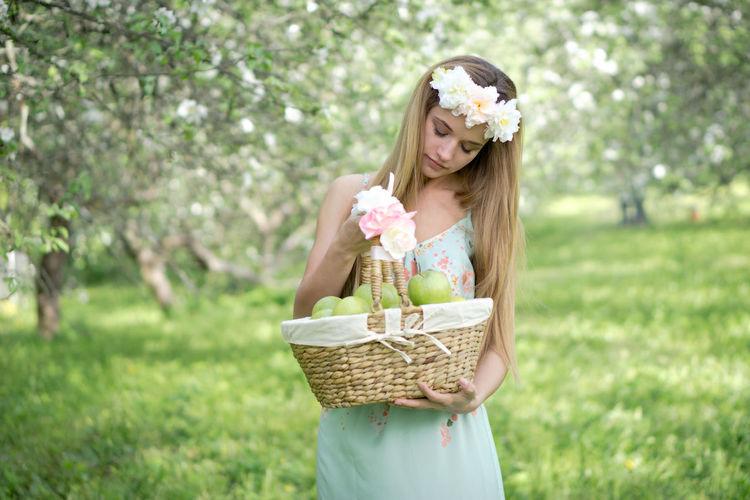 Woman wearing hat standing in basket on field