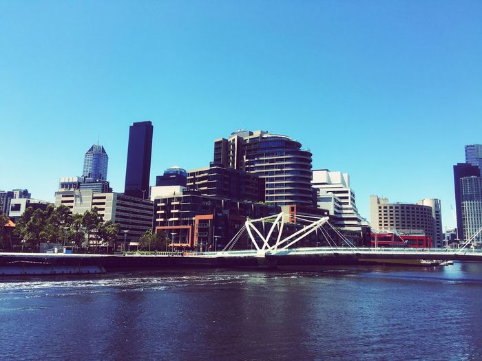 River By Buildings Against Clear Blue Sky