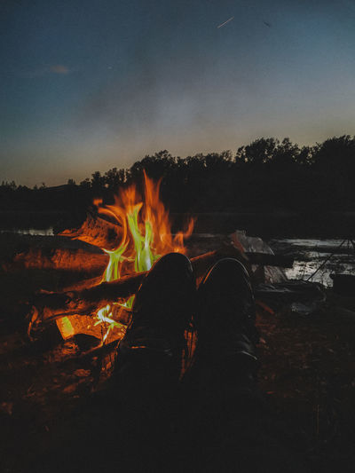 Low section of people relaxing on log at night
