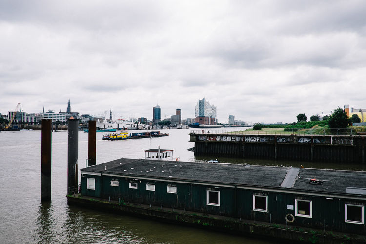 Houseboat moored in river against cityscape