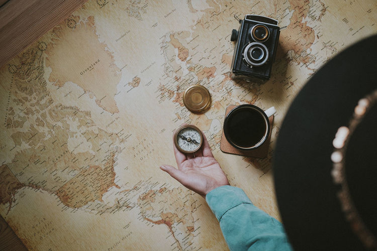 Cropped hand of person holding navigational compass by coffee cup with camera over world map