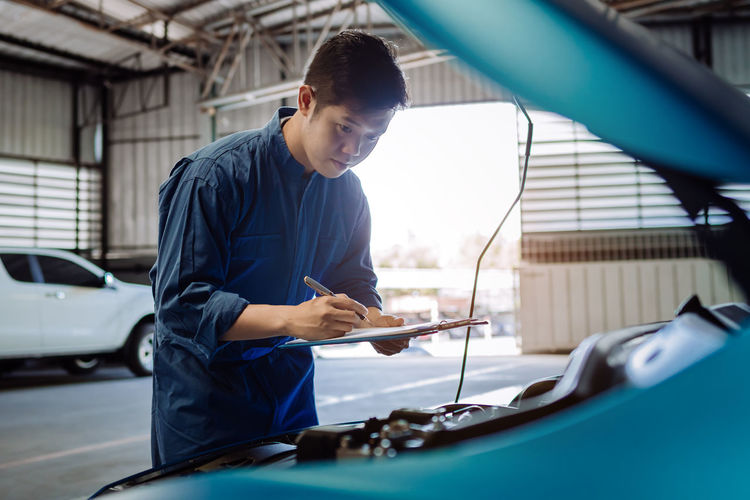 Mechanic examining car in garage