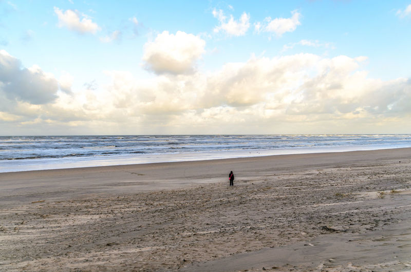 Lonesome woman at theempty beach in zandvoort Beach Beauty In Nature Cloud - Sky Day Full Length Horizon Over Water Leisure Activity Men Nature One Person Outdoors People Real People Sand Scenics Sea Shore Sky Tranquility Vacations Water Wave