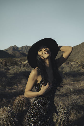 Woman wearing hat standing on mountain against sky