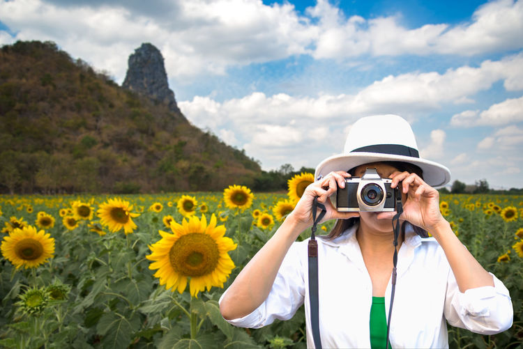 Woman photographing with yellow camera on land against sky