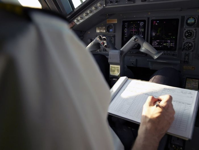 Pilot in the cockpit writing in the logbook Cockpit Aircraft Pilot