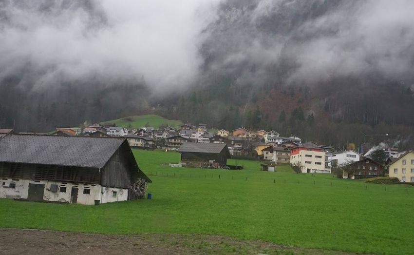 Houses on field by buildings against sky