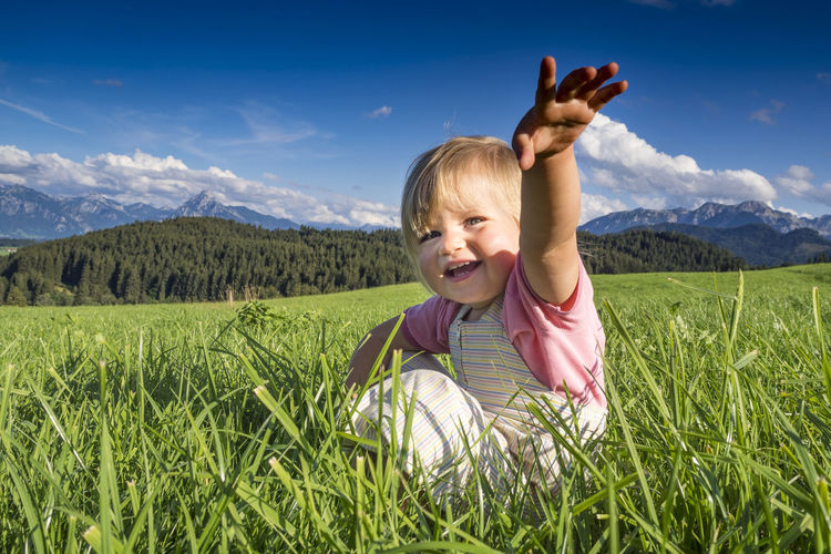 Portrait of smiling cute girl gesturing while sitting on grass against sky
