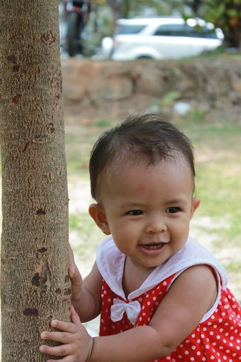 Cute baby girl by tree trunk